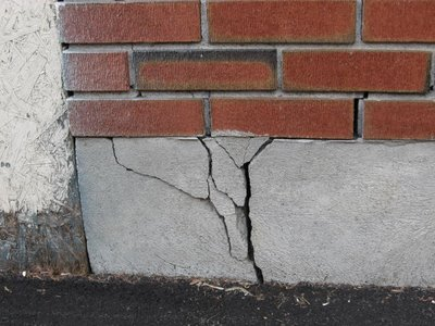 Трещины в цоколе - характерный признак воздействия сил пучения на фундамент дома